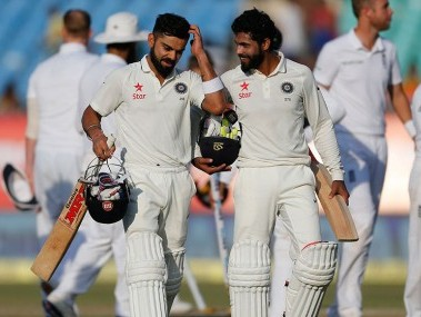 Virat Kohli and Ravindra Jadeja walk back after drawing the Rajkot Test. AP