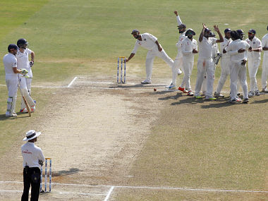 England's Jonny Bairstow and James Anderson watch Indian players celebrate their win. AP
