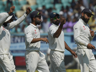 Virat Kohli (R) leads his team back to the dressing room. AFP