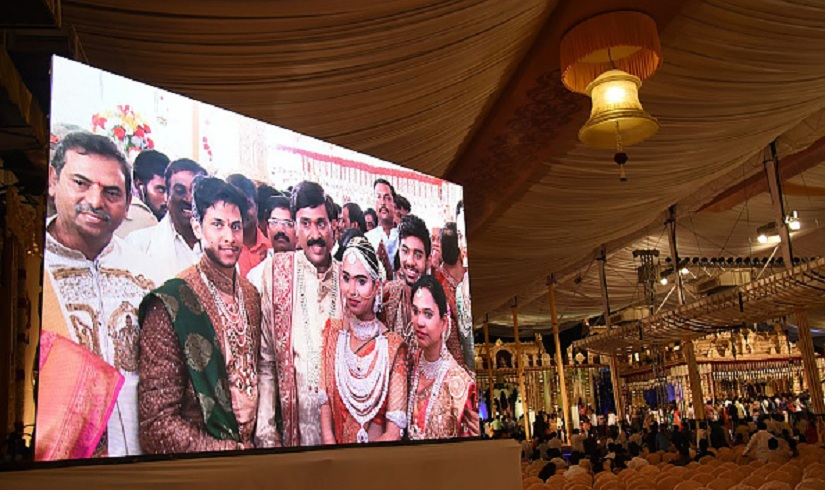Indian mining tycoon, Gali Janardhan Reddy, (C) is seen on a big screen as he poses with his daughter Brahmani (2R) and son-in-law, Rajeev Reddy (2L) during their wedding at the Bangalore Palace Grounds in Bangalore. A controversial Indian mining tycoon has taken over a royal palace and flown in Brazilian dancers at a reported cost of 75 million dollars to celebrate his daughter's wedding, as the country reels from a cash crisis. / AFP / STRINGER (Photo credit should read STRINGER/AFP/Getty Images)