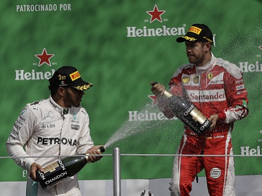 Lewis Hamilton of Mercedes celebrates with Ferrari's Sebastian Vettel after winning the Mexican Grand Prix. AP