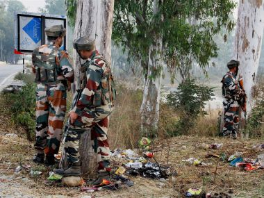 Security personnel take positions during a gun battle with suspected militants at the Army camp in Nagrota in Jammu, on Tuesday. PTI