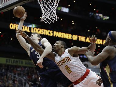 New Orleans Pelicans' Omer Asik grabs a rebound in front of Atlanta Hawks' Dwight Howard. AP