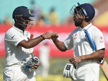 Cheteshwar Pujara and Murali Vijay bump fists on the third day of the first Test against England. AFP