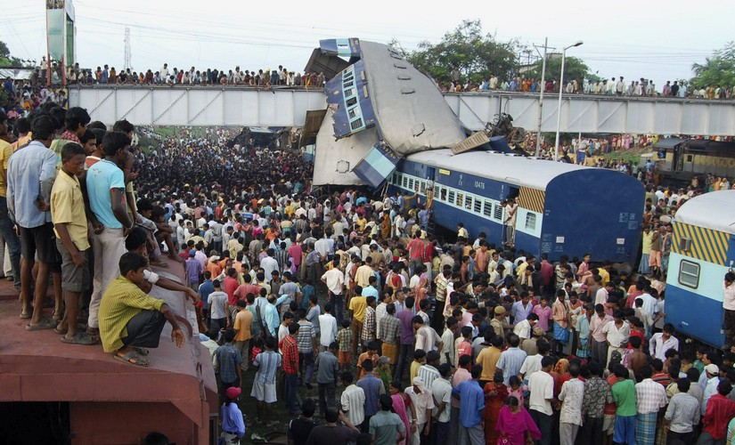 Onlookers stand at the site of a train accident at Sainthia in the eastern Indian state of West Bengal July 19, 2010. A speeding passenger train crashed into another waiting at a station in eastern India early on Monday, killing at least 60 people in India's second major accident in as many months, officials said. REUTERS/Stringer (INDIA - Tags: TRANSPORT DISASTER IMAGES OF THE DAY) - RTR2GJA4
