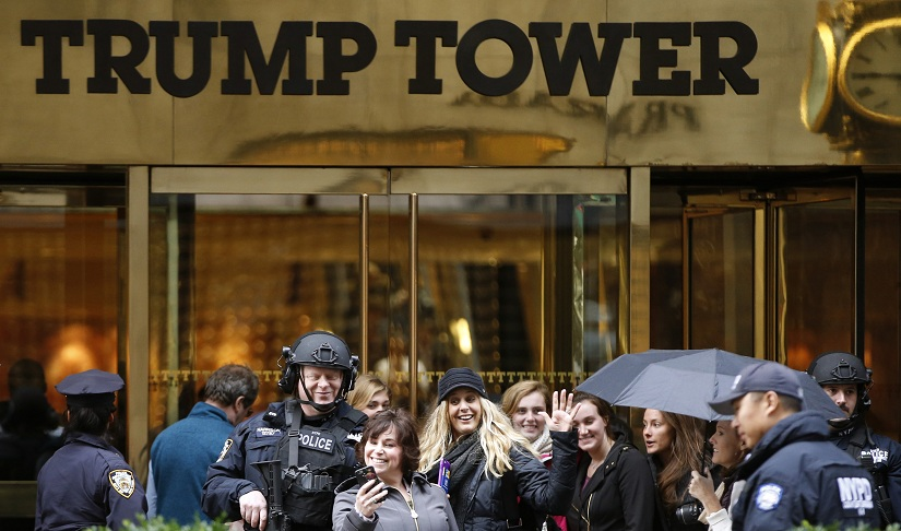 FILE - In this Nov. 15, 2016 file photo, a passersby stops for a selfie with a heavily-armed New York City police officer at the main, Fifth Avenue entrance to Trump Tower in New York. Outside Donald Trump's gilded skyscraper, many in the slow-moving sidewalk throng come for the sole purpose of snapping selfies, some to capture a bit of history and others to offer the new president their one-fingered salute. (AP Photo/Kathy Willens, File)