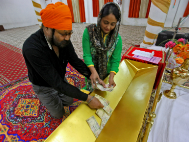 A couple puts Rs 500 and Rs 1,000 banknotes into a charity donation box inside a Gurudwara in Chandigarh on Thursday. Reuters