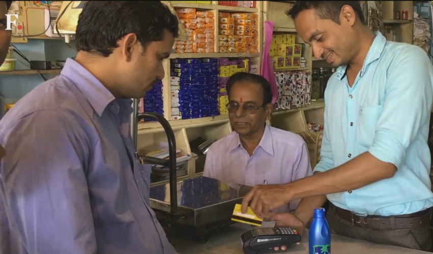 A customer uses debit card for buying groceries in Dhasai.