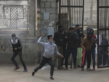 A protester throws a stone towards Indian policemen in Kashmir. AP