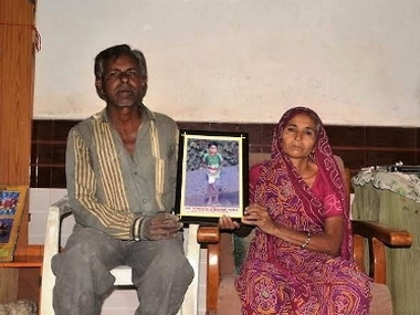 Jai's parents show a framed photograph of the 11-year-old at their one-room rented house in Junagadh, Gujarat. A Thalassemic patient since he was just a year old, Jai had contracted HIV through blood transfusion at the Junagadh Civil Hospital.