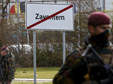 Belgian soldiers stand guard on a road leading to Zaventem airport . Reuters