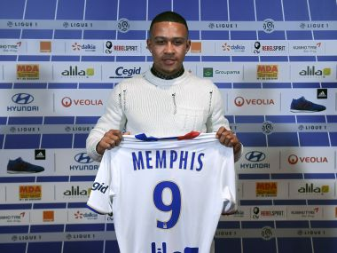 Memphis Depay poses with the Lyon jersey after his move from Manchester United. AFP
