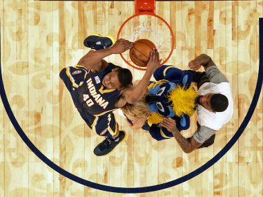 Glenn Robinson III slam dunks over teammate Paul George, a mascot, and a cheerleader. AP