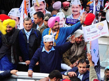 Arvind Kejriwal with party MP Bhagwant Mann and AAP MLA candidate in Patiala, Balbir Singh wave to their supporters during a road show in Patiala on Friday. PTI.