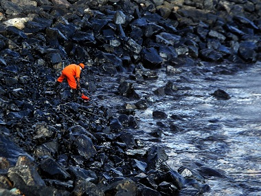 A volunteer cleaning up the sludge at Ennore. AFP.