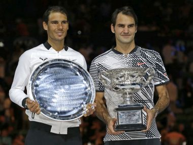 Roger Federer and Rafael Nadal hold their trophies after the Australian Open final. AP