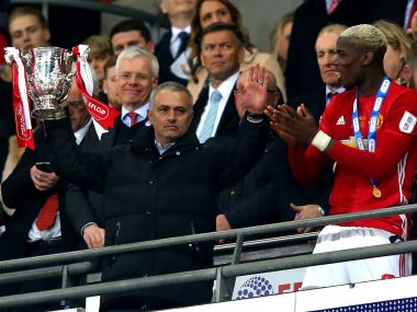 Manchester United manager Jose Mourinho (left) lifts the League Cup trophy in alongside Paul Pogba on Sunday. Getty Images