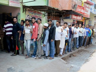 Voters queue up to caste their votes during the third phase of UP assembly election in Kanpur on Sunday. PTI