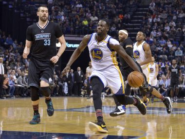 Golden State Warriors' Draymond Green drives the ball on a fast break past Memphis Grizzlies players. AP