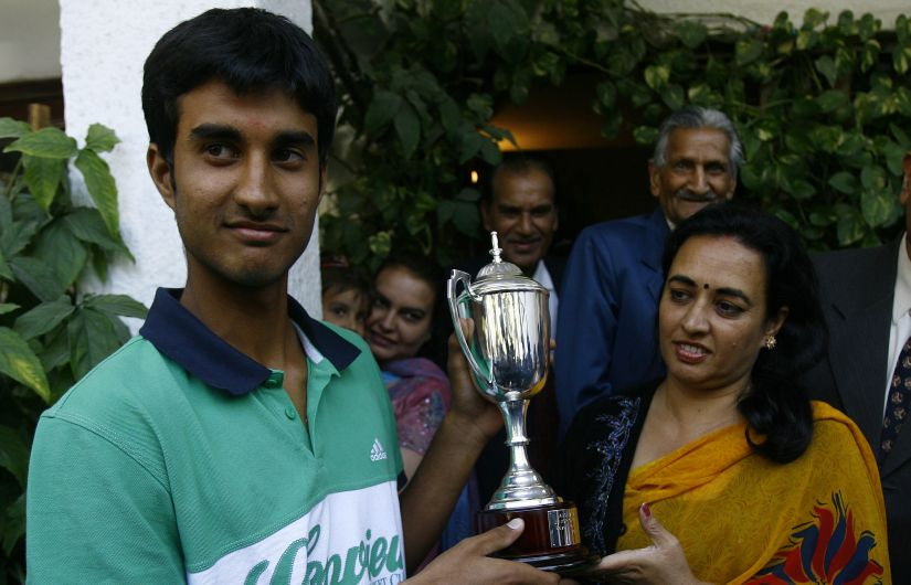 File photo of winner of 2009 Junior Australian Open Yuki Bhambri holding his trophy along with his mother Indu Bhambri. AFP