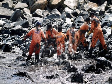 Firefighters and volunteers try to clean up oil that has washed ashore, in Chennai on Saturday. PTI