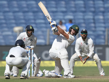 Australia's Mitchell Starc plays a shot as the Indian fielders look on during Day 1 of the 1st Test cricket in Pune. AFP
