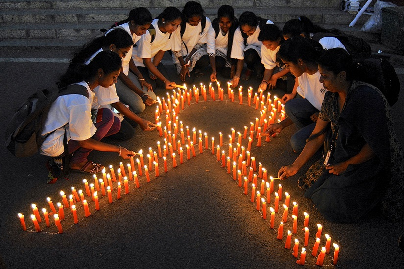 Staff members of a government-run pharmaceutical college light candles arranged in the formation of a ribbon to promote cancer awareness and mark World Cancer Day, in the southern Indian city of Bengaluru, formerly known as Bangalore, February 4, 2015. REUTERS/Abhishek N. Chinnappa (INDIA - Tags: HEALTH SOCIETY ANNIVERSARY) - RTR4O7YR