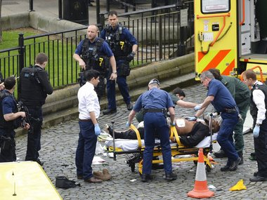 "A man is treated by emergency services as police look on at the scene outside the Houses of Parliament London, Wednesday, March 22, 2017. London police say they are treating a gun and knife incident at Britain's Parliament ""as a terrorist incident until we know otherwise."" The Metropolitan Police says in a statement that the incident is ongoing. It is urging people to stay away from the area. Officials say a man with a knife attacked a police officer at Parliament and was shot by officers. Nearby, witnesses say a vehicle struck several people on the Westminster Bridge. AP"