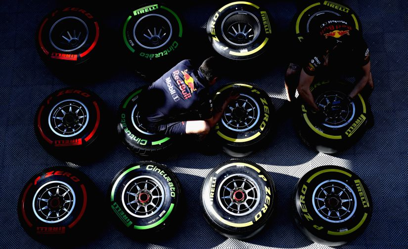 Red Bull Racing team members work on tyres in the Paddock during the Formula One winter testing. Getty