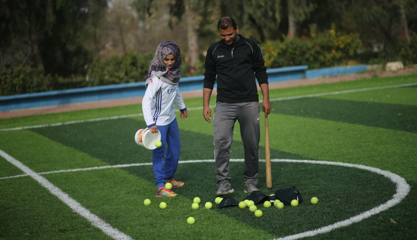 Palestinian baseball coach Mahmoud Tafesh uses a makeshift bat and tennis balls during baseball training session for women. Reuters