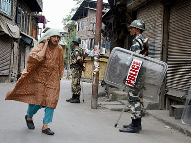 An elderly woman walks past security jawans standing guard in a street during curfew in Srinagar on Sunday. PTI