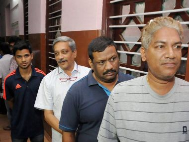 Defence Minister Manohar Parrikar stands in a queue outside a polling booth in Goa on 4 February. PTI