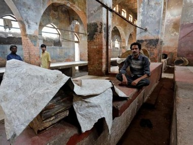 A worker sits inside a closed mutton market in Lucknow. Reuters