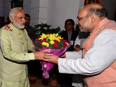 New Delhi: Prime Minister Narendra Modi being welcomed by party president Amit Shah at the party headquarters to celebrate victory in UP and Uttrakhand Assembly elections, in New Delhi on Sunday. PTI