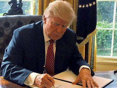 US President Donald Trump signing a revised executive order. PTI