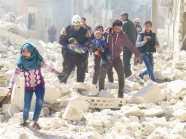 People and a civil defence personnel carry children at a damaged site after an air strike on rebel-held Idlib city, Syria. Reuters