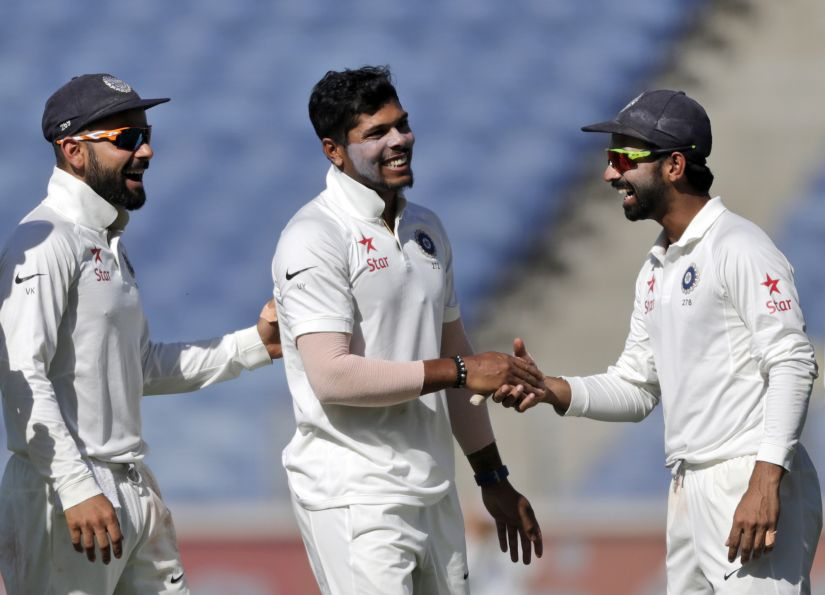 India's Umesh Yadav, centre, with Virat Kohli, left, and Ajinkya Rahane during the first Test. AP