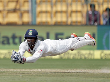 Wriddhiman Saha dives forward to collect Steve O'Keefe's catch in the second Test in Bengaluru. AP