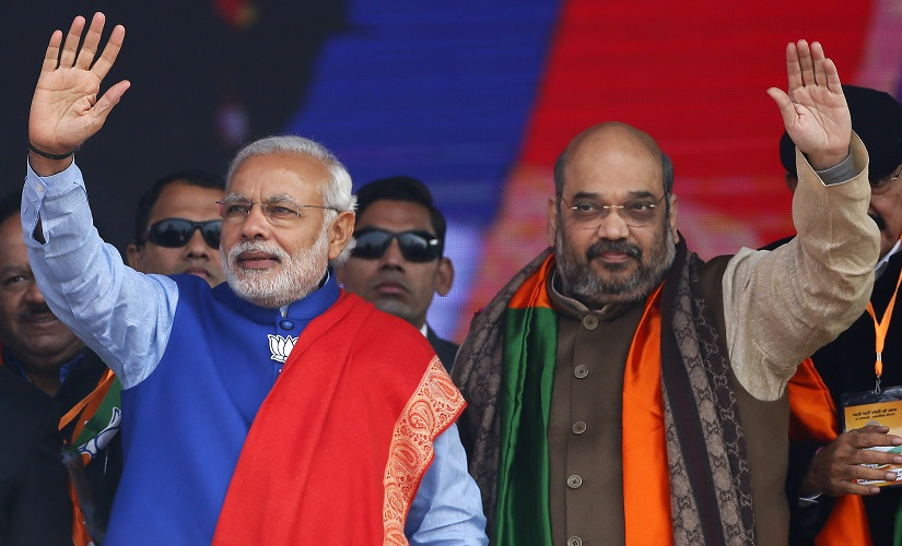 Indian Prime Minister Narendra Modi (L) and Amit Shah, the president of India's ruling Bharatiya Janata Party (BJP), wave to their supporters during a campaign rally ahead of state assembly elections, at Ramlila ground in New Delhi January 10, 2015. REUTERS/Anindito Mukherjee (INDIA - Tags: POLITICS ELECTIONS) - RTR4KTIV