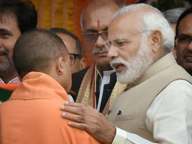 Prime Minister Narendra Modi speaks with UP Chief Minister Yogi Adityanath after the swearing-in ceremony in Lucknow on Sunday. PTI