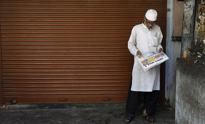 A Muslim man reads a newspaper as he stands outside a closed shop in Lucknow