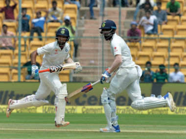 India's KL Rahul (R) and Cheteshwar Pujara run between the wickets in second Test against Australia in Bangalore. AFP
