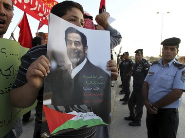 A boy holds a picture of late Iraqi President Saddam Hussein. File photo. Reuters