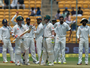 Steve Smith (C), David Warner and the Indian team wait for the third umpire's decision on Day 4 of the Bengaluru Test. AFP
