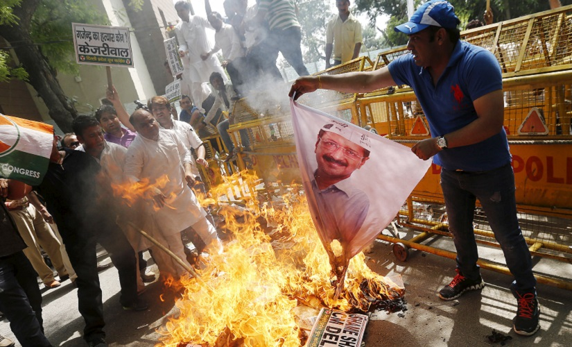 An activist of the youth wing of India's opposition Congress party burns a banner of Arvind Kejriwal, chief of Aam Aadmi (Common Man) Party (AAP) and Chief Minister of Delhi, during a protest over the suicide by a farmer at a rally on Wednesday, in New Delhi April 23, 2015. A farmer hanged himself from a tree during a political rally organised by the Aam Aadmi Party (AAP) in New Delhi on Wednesday, in what appeared to be a desperate protest against the hardship felt by many people scratching a living in rural India. REUTERS/Adnan Abidi - RTX19Y1M