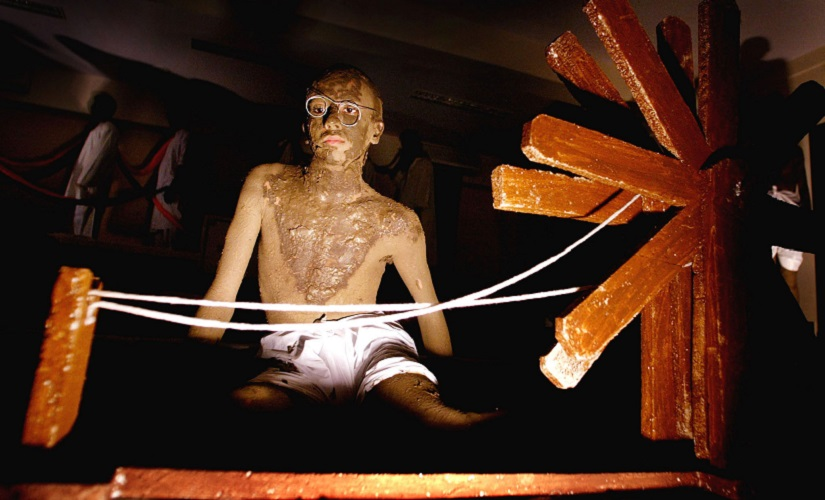 An Indian college student, smeared with clay to resemble Mahatma Gandhi, sits beside a spinning wheel during an event to mark the 55th anniversary of the death of Gandhi in Bombay January 30, 2003. Students from a city college reenacted several scenes from Gandhi's freedom struggle against the British colonial rule. The day is observed as 'Martyr's Day' in the country. REUTERS/Arko Datta AD/CP - RTRHG9P
