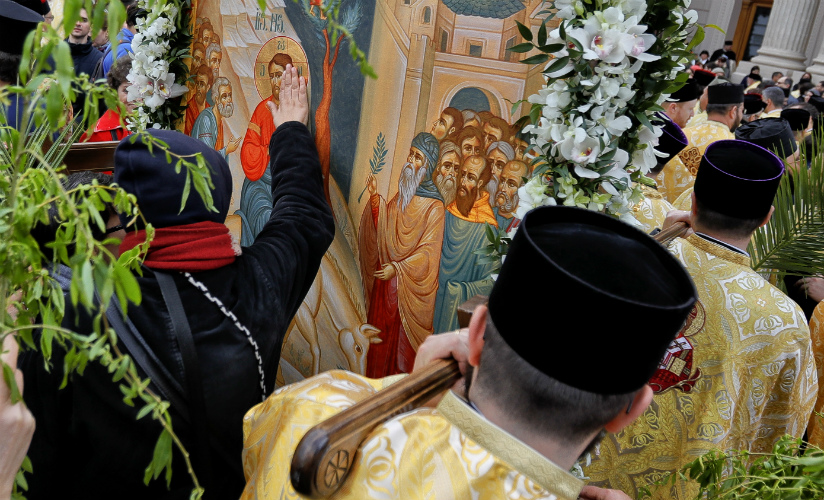 In this Saturday, April 8, 2017, picture a woman touches a large icon carried by Romanian Orthodox priests after a service ahead of Palm Sunday in Bucharest, Romania. AP