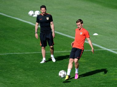 Antoine Griezmann of Atletico Madrid passes the ball as Diego Simeone watches during a training session. Getty