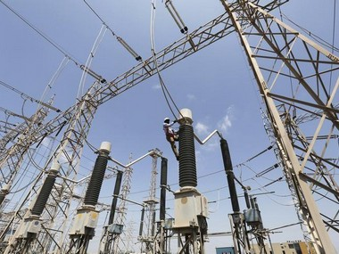 A technician repairs power supply lines at a power plant of Adani Power at Mundra Port in Gujarat . Reuters.