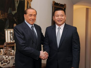 Chinese businessman Yonghong Li, right, shakes hands with Silvio Berlusconi. AP